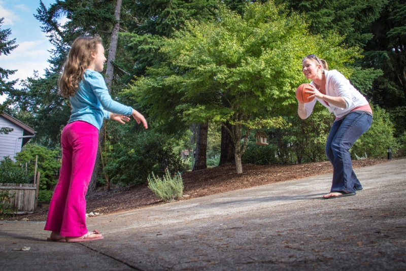 Researcher Megan MacDonald practices throwing a ball with a young girl.