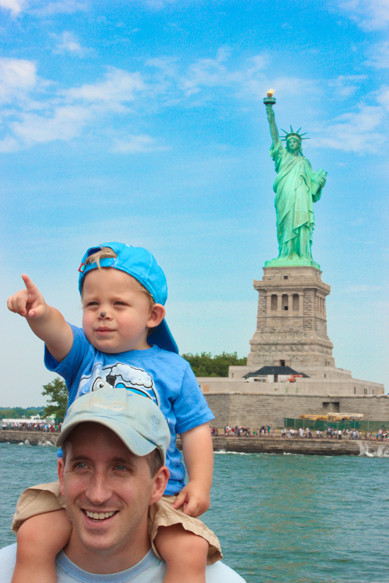 boy and father at statue of liberty