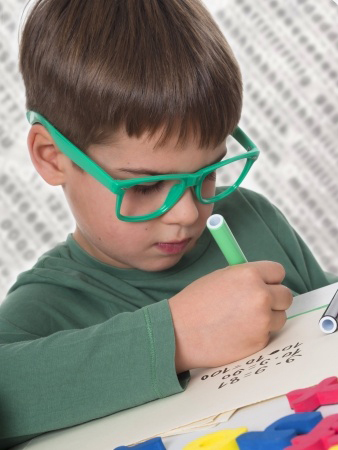 little boy wearing glasses doing homework