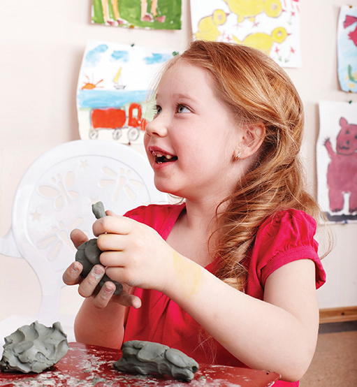 young girl sculpting clay at arts and crafts camp