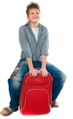 boy sitting on overnight bag