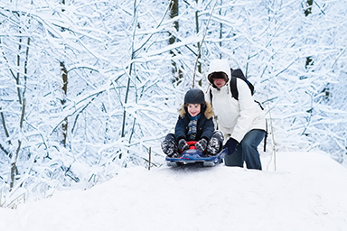 child wearing helmut while sledding