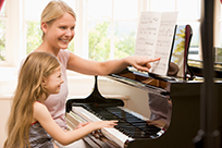child playing piano with teacher