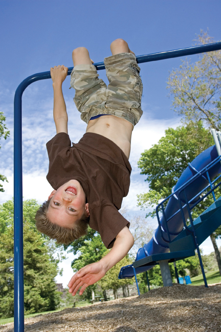 boy hanging upside down on playground