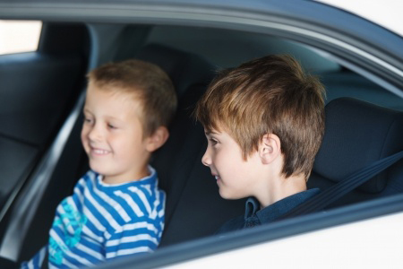 two young boys in backseat of a car