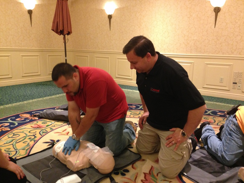 man practices cpr with aed