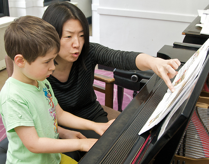 child and teacher at piano